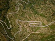 Vista aérea de una ruta de la montaña con las curvas cerca al volcán del Etna, Sicilia, Italia Edificio y coche arruinados foto de archivo libre de regalías
