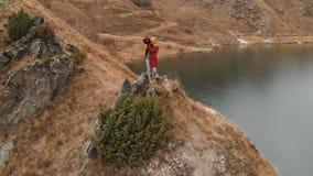 Vista aérea de una situación de la muchacha en una roca en la orilla de un lago, que fotografía el paisaje en su cámara de DSLR metrajes