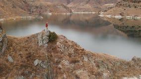 Vista aérea de una situación de la muchacha en una roca en la orilla de un lago V?deos del viaje almacen de metraje de vídeo