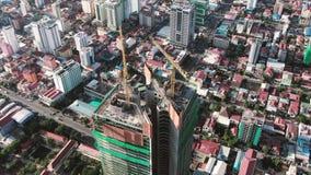 Vista aérea de una torre residencial y de la oficina combinada bajo construcción en Asia: círculos de la cámara lentamente 60 fps metrajes