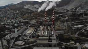Vista aérea de 3 vermelhos e das tubulações brancas com poluição branca do produto do fumo à atmosfera contra o contexto do vídeos de arquivo