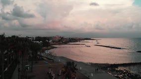Vista aérea del área despoblada del turista y de la playa con los sunbeds y los paraguas vacantes por la tarde Abejón tirado de w almacen de metraje de vídeo