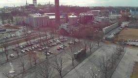 Vista aérea del aparcamiento grande con los coches cerca de los edificios modernos e históricos y chimenea roja alta en el centro almacen de video