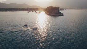 Vista aérea del barco de la natación en bahía del mar en puesta del sol metrajes