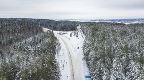 Vista aérea del bosque cubierta con la nieve, camino en invierno imágenes de archivo libres de regalías