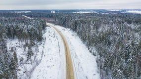 Vista aérea del bosque cubierta con la nieve, camino en invierno imagen de archivo