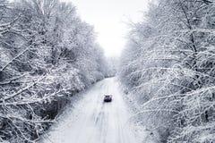 Vista aérea del bosque nevoso con un camino Foto de archivo