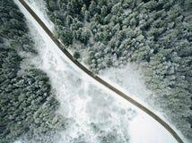 Vista aérea del bosque nevoso con un camino Foto de archivo libre de regalías
