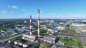 Vista aérea del calor y de la central eléctrica con las chimeneas rayadas rojas y blancas en zona industrial cantidad Industria p metrajes