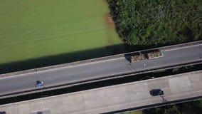 Vista aérea del camión de la madera que conduce a través del puente sobre el río coloreado verde Vuelo cinemático del tiro del ab almacen de metraje de vídeo