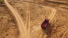 Vista aérea del camión rojo grande vacío que mueve encendido una pista arenosa para la arena en desierto o dunas Hermosa vista de almacen de video