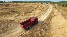 Vista aérea del camión volquete rojo que mueve encendido el camino de la arena en una mina cerca del bosque en día de verano esce almacen de video