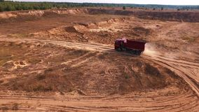 Vista aérea del camión volquete rojo que mueve encendido el camino rojo de la arena en una mina cerca del bosque en día de verano almacen de video
