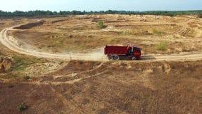 Vista aérea del camión volquete rojo que mueve encendido el camino de la arena en una mina cerca del bosque en día de verano esce metrajes