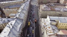 Vista aérea del camino ancho por completo de los coches que montan de diversos colores entre edificios almacen de video