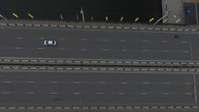 Vista aérea del camino ancho del puente con muchos coches del montar a caballo en ella sobre el río oscuro almacen de metraje de vídeo