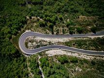 Vista aérea del camino de la curva con un coche en la montaña con el bosque verde en Croacia Imagen de archivo libre de regalías