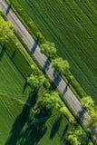 Vista aérea del camino del pueblo y de los campos verdes de la cosecha imagenes de archivo