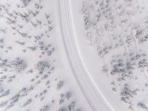 Vista aérea del camino en el bosque de la nieve del invierno en Finlandia Imagen de archivo