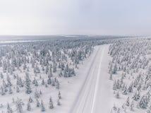 Vista aérea del camino en el bosque de la nieve del invierno en Finlandia Imagen de archivo libre de regalías