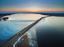 Vista aérea del camino en el lago congelado con los coches móviles en sunse Foto de archivo libre de regalías