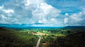 Vista aérea del camino que pasa a través de la montaña media del campo y del cielo azul imagen de archivo libre de regalías