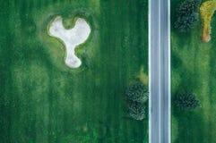 Vista aérea del camino a través del campo verde hermoso Fotos de archivo libres de regalías