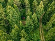 Vista aérea del camino a través de la cabina roja del bosque spruce en el bosque en Finlandia Fotos de archivo
