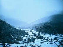 Vista aérea del campo y de casas de niebla en valle nevoso Colinas y montañas con el bosque del árbol de pino cubierto en nieve imagen de archivo libre de regalías