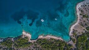 Vista aérea del catamarán y del yate en el mar cerca de la isla griega fotos de archivo libres de regalías