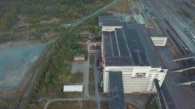 Vista aérea del edificio industrial gris enorme cerca de la tierra ferroviaria e inútil, rodeada por zona industrial del bosque d metrajes