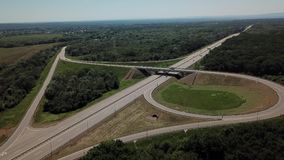 Vista aérea del empalme de camino de la carretera de la hoja de trébol en el campo con los árboles almacen de video