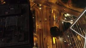 Vista aérea del empalme de camino moderno, de los edificios y de los coches móviles en la noche existencias Camino del tráfico de almacen de metraje de vídeo