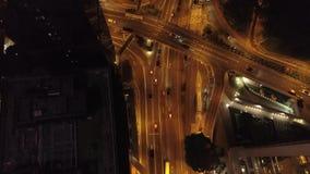 Vista aérea del empalme de camino moderno, de los edificios y de los coches móviles en la noche existencias Camino del tráfico de metrajes