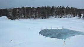 Vista aérea del lago congelado cerca de los árboles coníferos en invierno contra el cielo gris cantidad Naturaleza hermosa del in metrajes