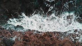Vista aérea del océano tempestuoso que golpea la playa rocosa Tiro del abejón del primer de las ondas del mar que crean espuma y  almacen de metraje de vídeo