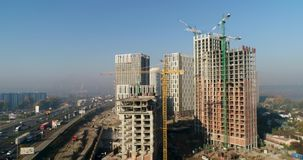 Vista aérea del paisaje en la ciudad con los edificios inferiores de la construcción y las grúas industriales Emplazamiento de la almacen de metraje de vídeo