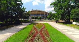 Vista aérea del parque del jardín del mar de Varna Bulgaria con las flores y del palacio de la cultura y de los deportes, centro  metrajes