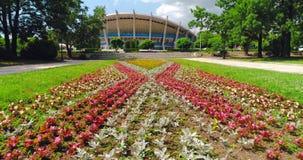 Vista aérea del parque del jardín del mar de Varna Bulgaria con las flores y del palacio de la cultura y de los deportes, centro  almacen de metraje de vídeo