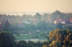 Vista aérea del pequeño campo en la costa del río en el bosque Fotos de archivo
