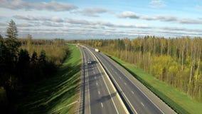 Vista aérea del petrolero moderno de la gasolina que viaja en el camino o la carretera en el fondo del bosque y del cielo almacen de video