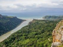Vista aérea del río marrón rodeada por el bosque que fluye en el océano en la costa salvaje del ` s de Suráfrica Fotografía de archivo