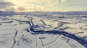 Vista aérea del río que atraviesa el campo nevado en la puesta del sol Imagen de archivo libre de regalías