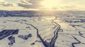 Vista aérea del río que atraviesa el campo nevado en la puesta del sol Foto de archivo