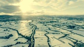 Vista aérea del río que atraviesa el campo nevado en la puesta del sol Foto de archivo libre de regalías