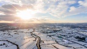 Vista aérea del río que atraviesa el campo nevado en la puesta del sol Fotografía de archivo
