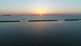 Vista aérea del rompeolas de la piedra en la puesta del sol almacen de metraje de vídeo