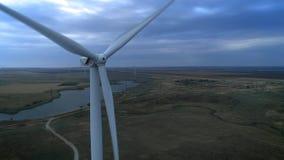 Vista aérea del tiro aéreo de la producción energética de las turbinas de viento 4k en puesta del sol turbinas de la cantidad del almacen de metraje de vídeo