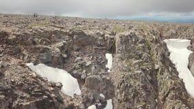 Vista aérea del top de la montaña con muchas piedras y de un glaciar de la nieve en el verano en las montañas del Altai con grand metrajes