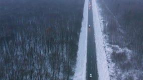 Vista aérea del tráfico en el camino que pasa a través del bosque del invierno en tiempo severo metrajes